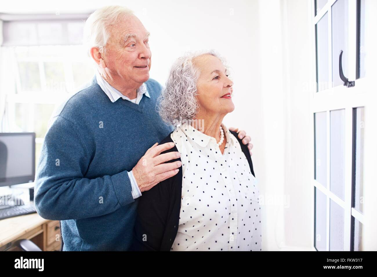 Senior couple in office looking out of window smiling - Stock Image