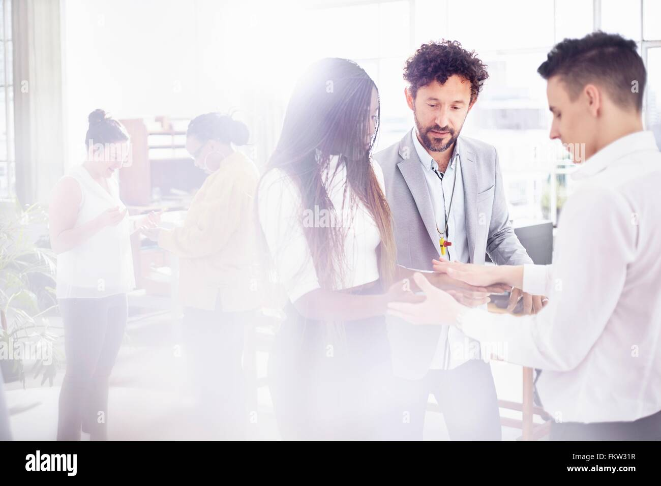 Colleagues in team building task face to face holding hands - Stock Image
