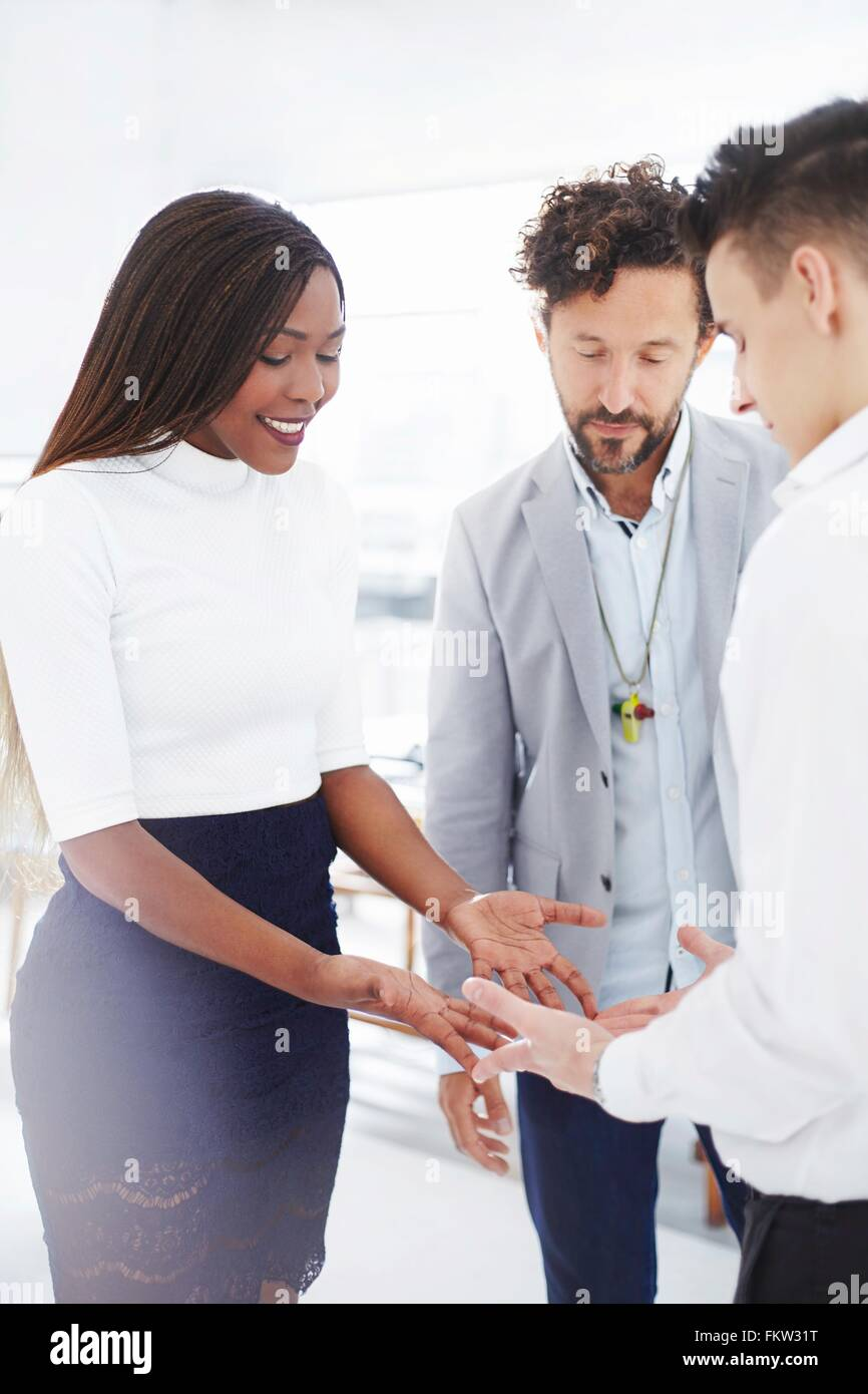 Colleagues in team building task face to face holding hands looking down smiling - Stock Image