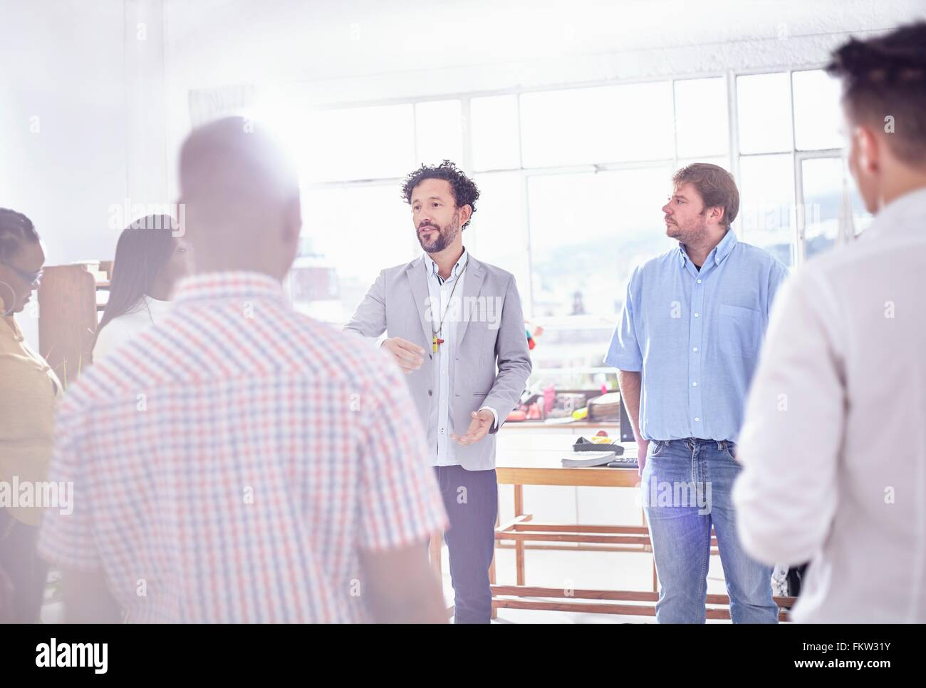 Mature man in  fice speaking to colleagues - Stock Image