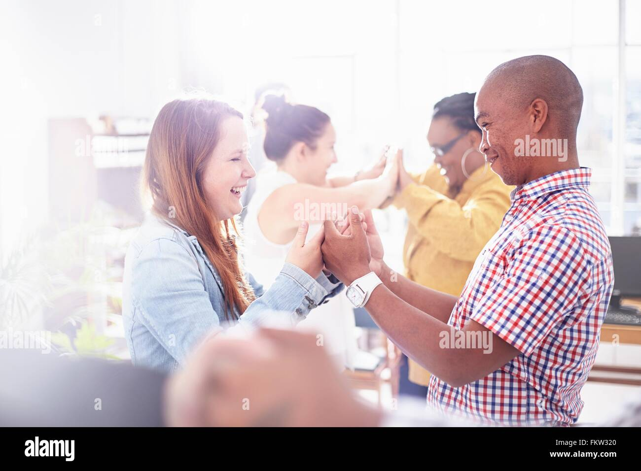 Side view   colleagues in team building task, face to face, hands together smiling - Stock Image