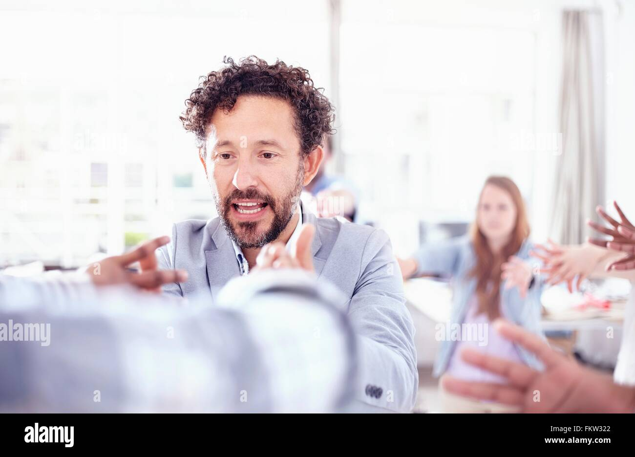 Bearded mature man in team building talk hands raised smiling - Stock Image