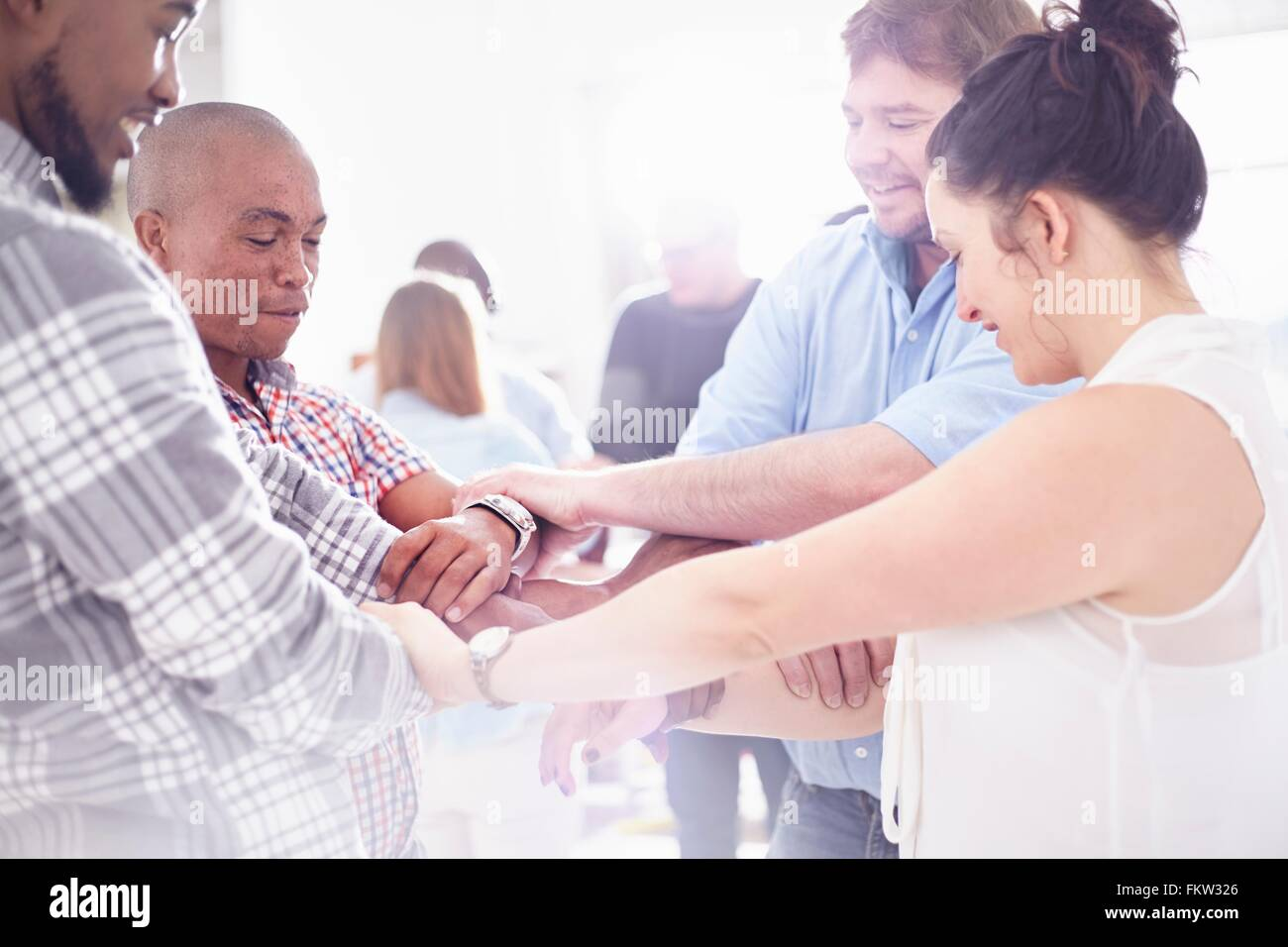 Side view   colleagues in team building task holding wrists smiling - Stock Image