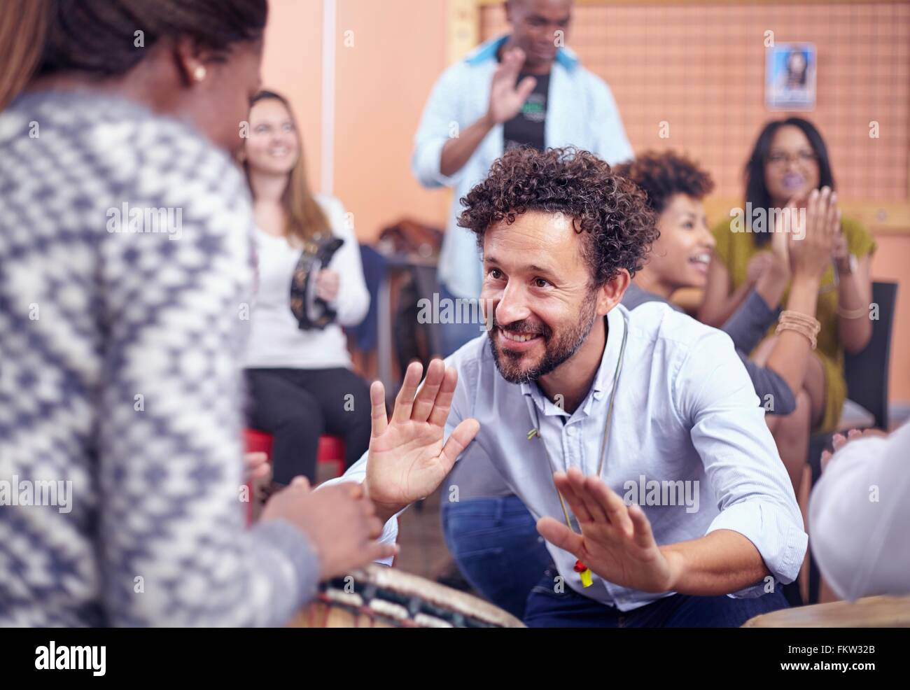 Friends playing musical instruments and dancing, smiling - Stock Image