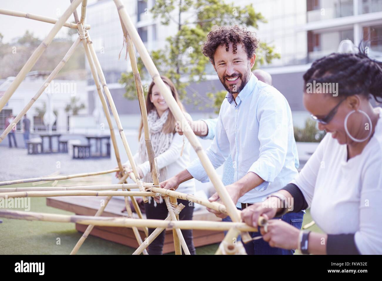 Colleagues in team building task building wooden structure smiling - Stock Image