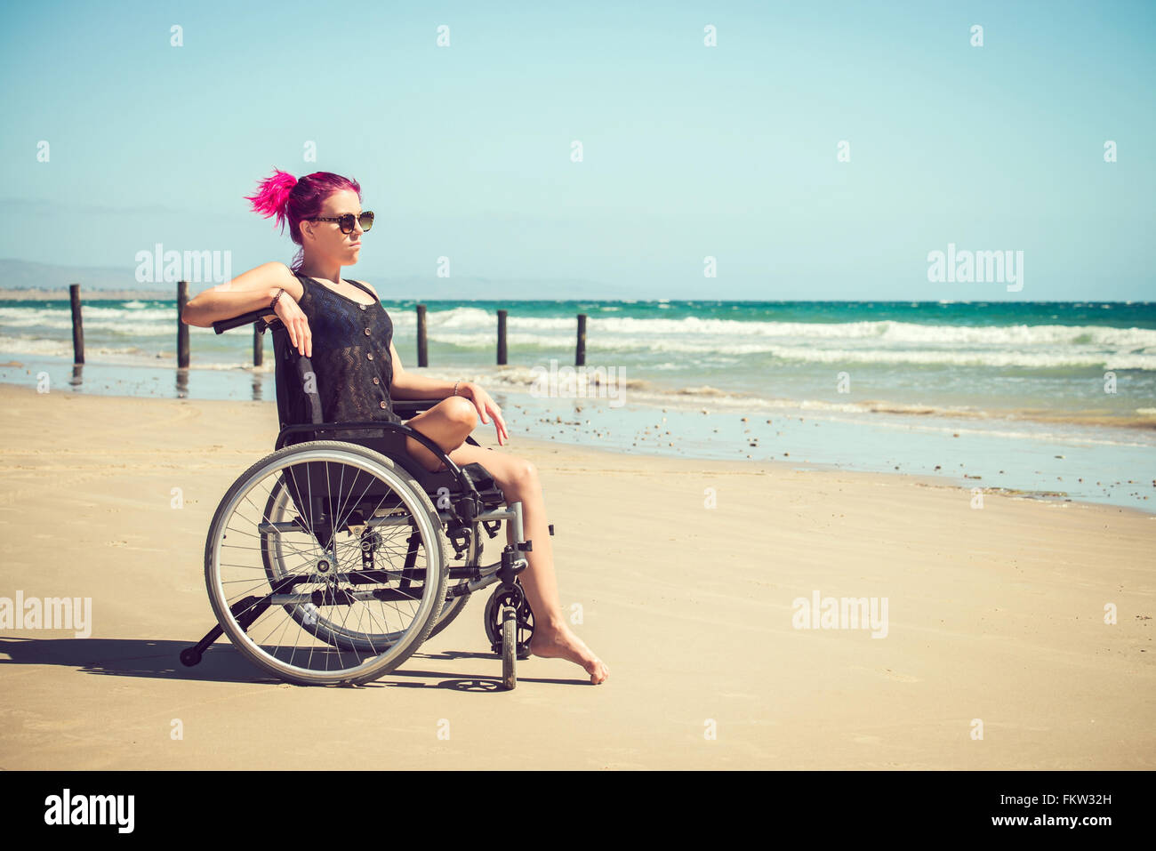 Disabled woman in the wheelchair at the beach. Cross-processed and color-toned image. - Stock Image