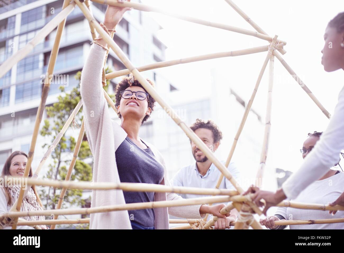 Low angle view   colleagues in team building task building wooden structure - Stock Image