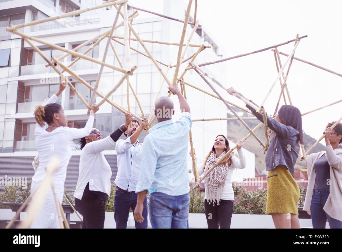 Low angle view   colleagues in team building task lifting building wooden structure - Stock Image