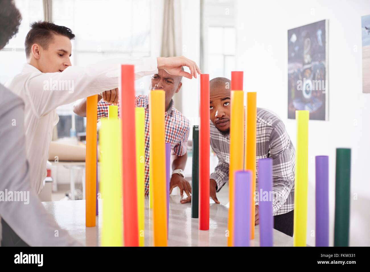 Colleagues in team building task balancing colourful tubes - Stock Image