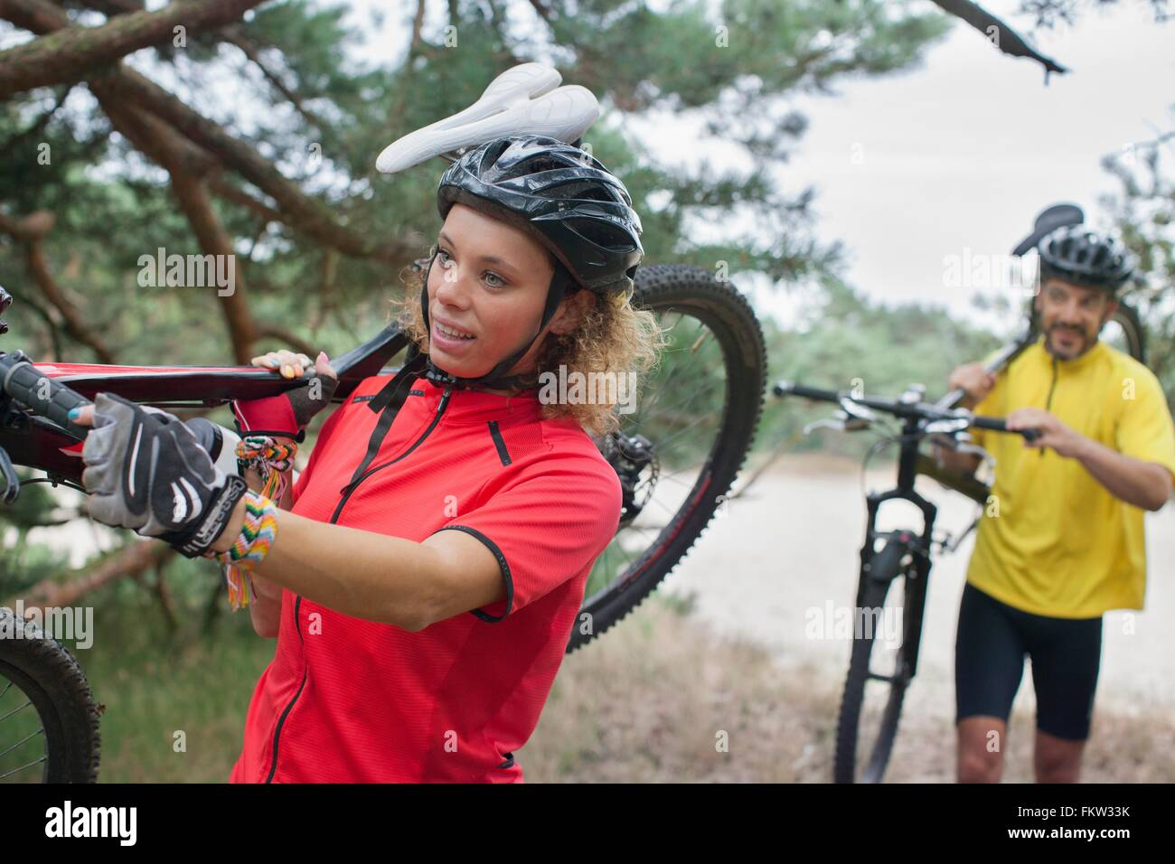 Mountain biking couple carrying cycles over sand on riverbank - Stock Image