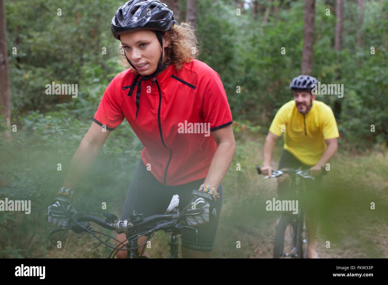 Mountain biking couple biking through forest - Stock Image