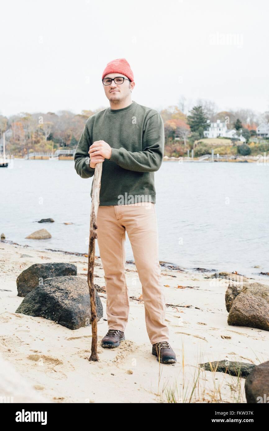 Portrait of mid adult man, holding walking stick, beside lake - Stock Image