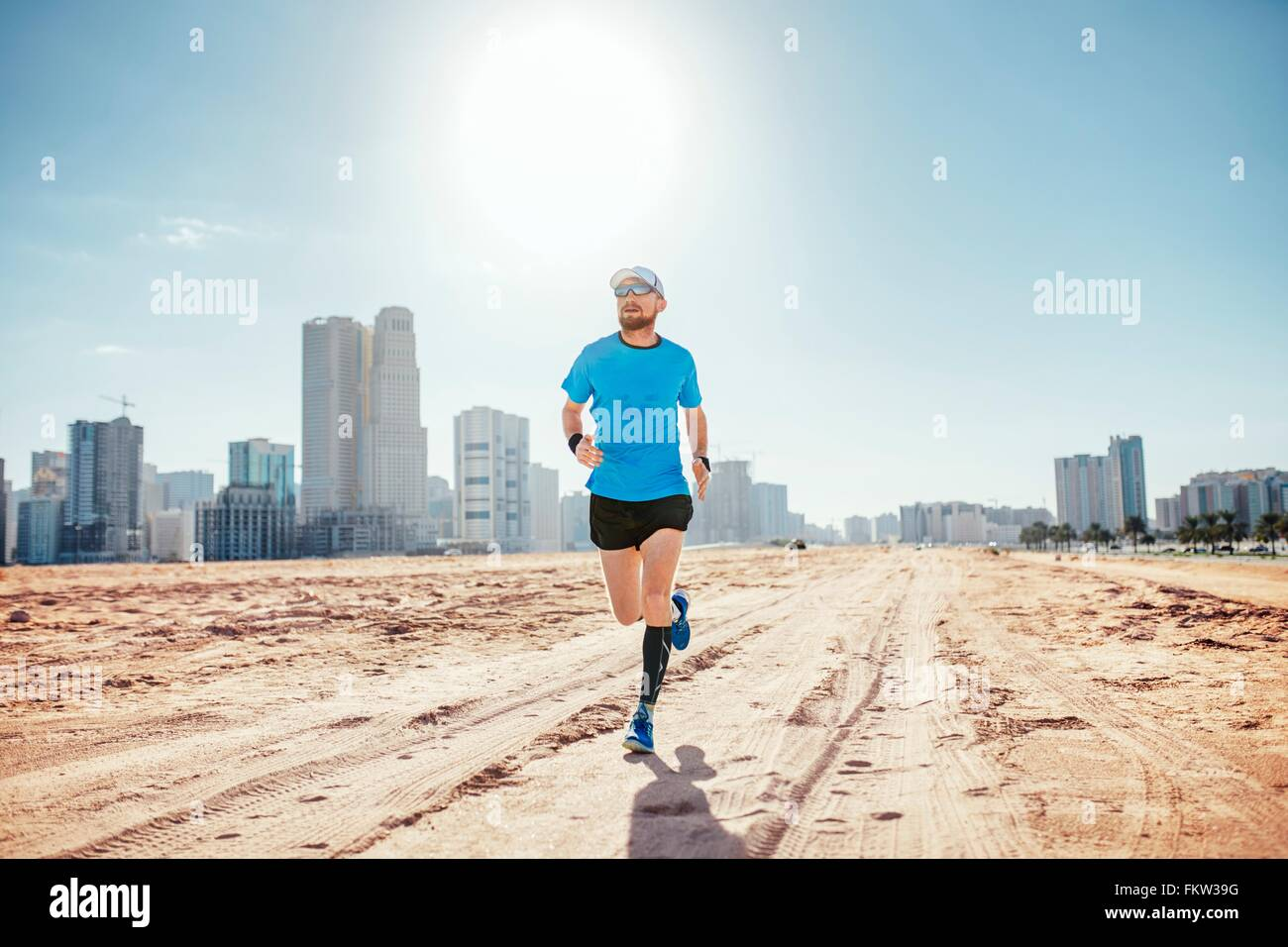 Full length front view of mid adult man running on sand by sky scrapers, Dubai, United Arab Emirates - Stock Image