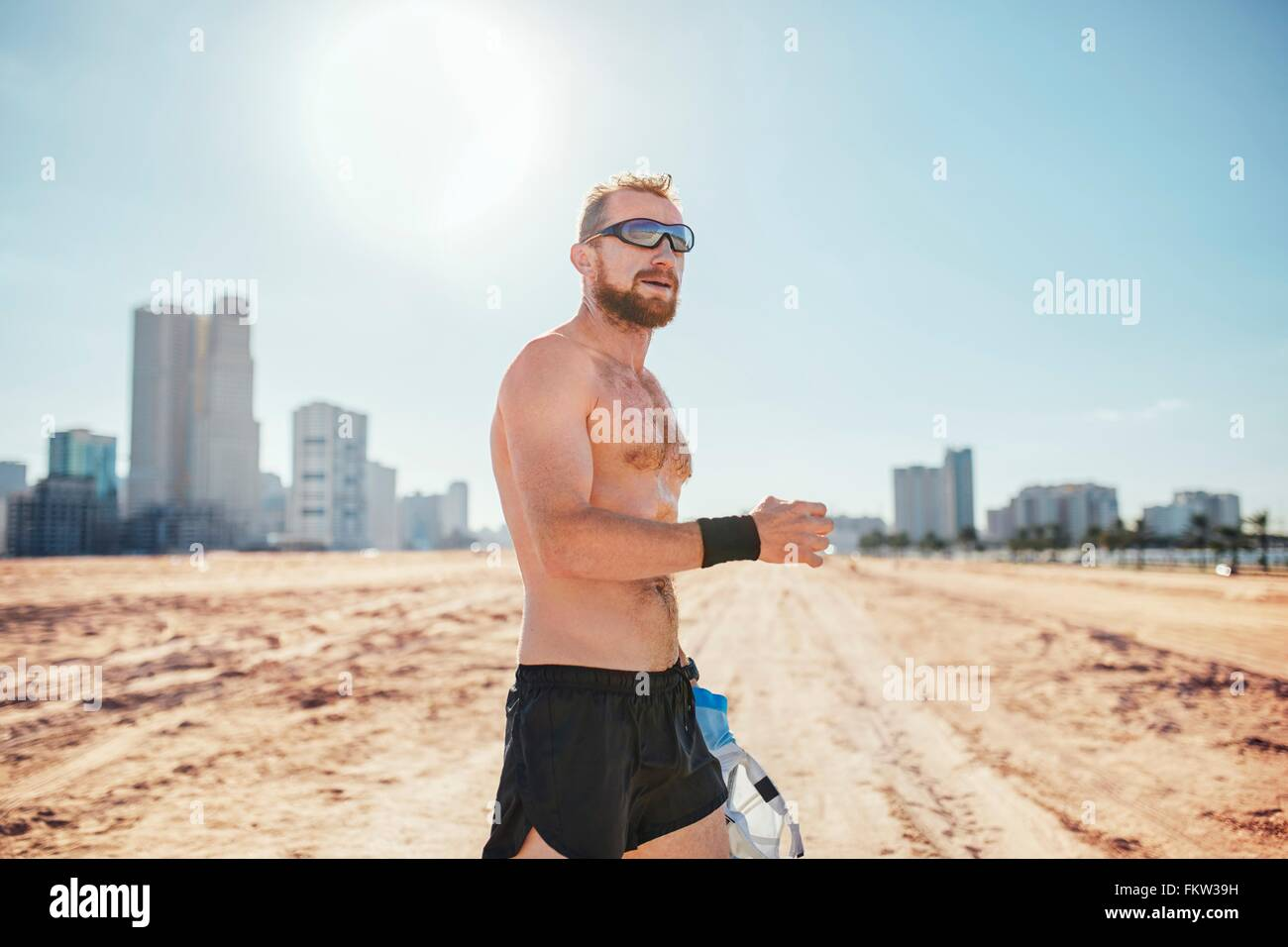 Barechested man on sand wearing sunglasses by skyscrapers, Dubai, United Arab Emirates - Stock Image