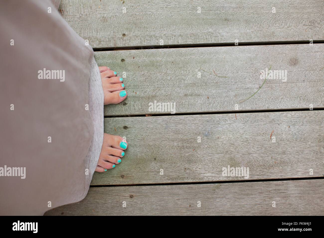Overhead view of female toes painted with turquoise nail varnish - Stock Image