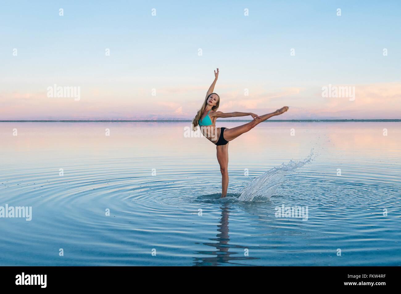 Female ballet dancer poised on one leg in lake, Bonneville Salt Flats, Utah, USA Stock Photo