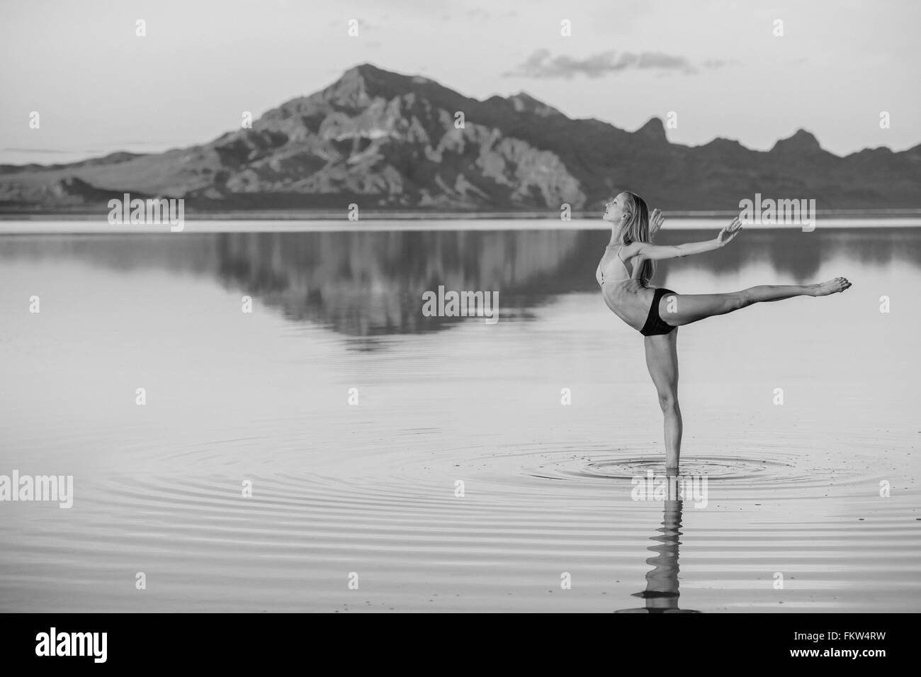 B&W of female ballet dancer in ballet position in lake, Bonneville Salt Flats, Utah, USA Stock Photo