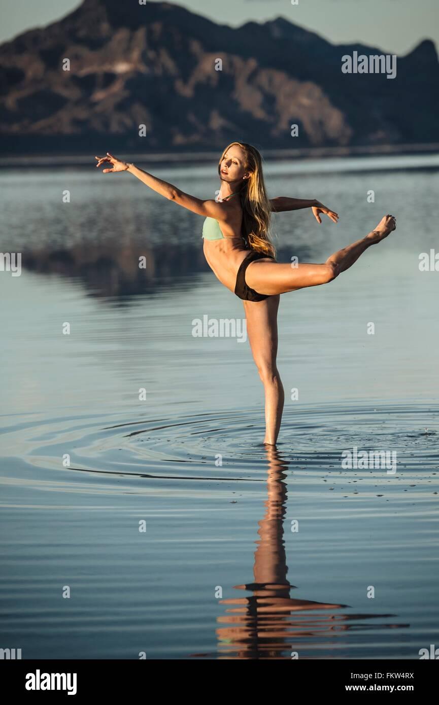 Female ballet dancer in ballet position in lake, Bonneville Salt Flats, Utah, USA Stock Photo
