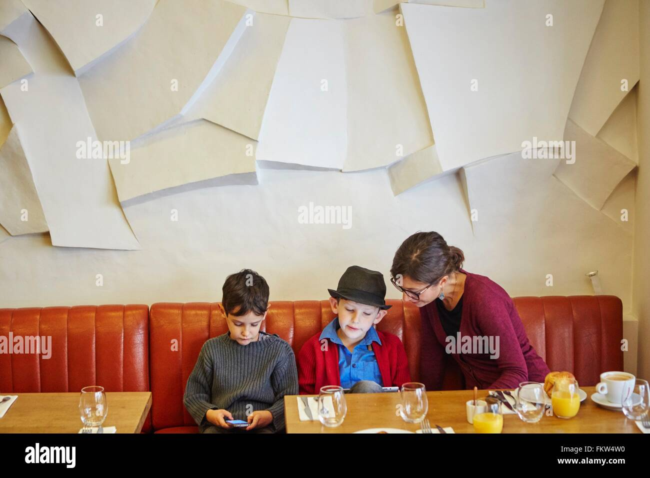 Mother and sons using digital tablet and smartphone in restaurant - Stock Image