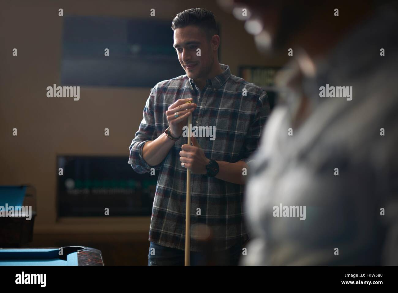 Man with pool cue standing at pool table - Stock Image