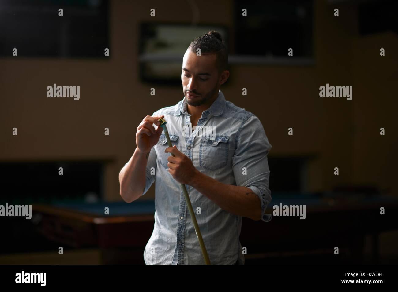 Man chalk rubbing pool cue - Stock Image