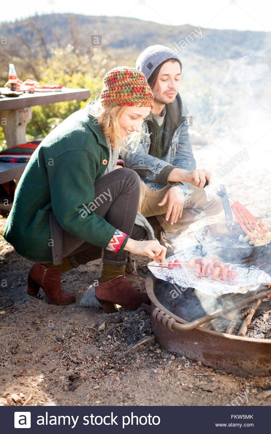 Young couple cooking food outdoors, in rural setting - Stock Image