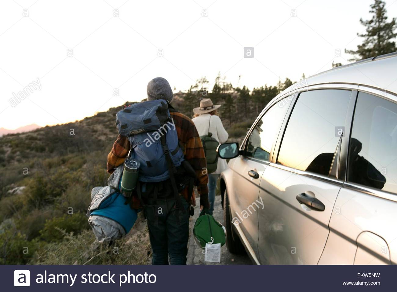 Young couple walking away from parked car carrying camping equipment, rear view - Stock Image