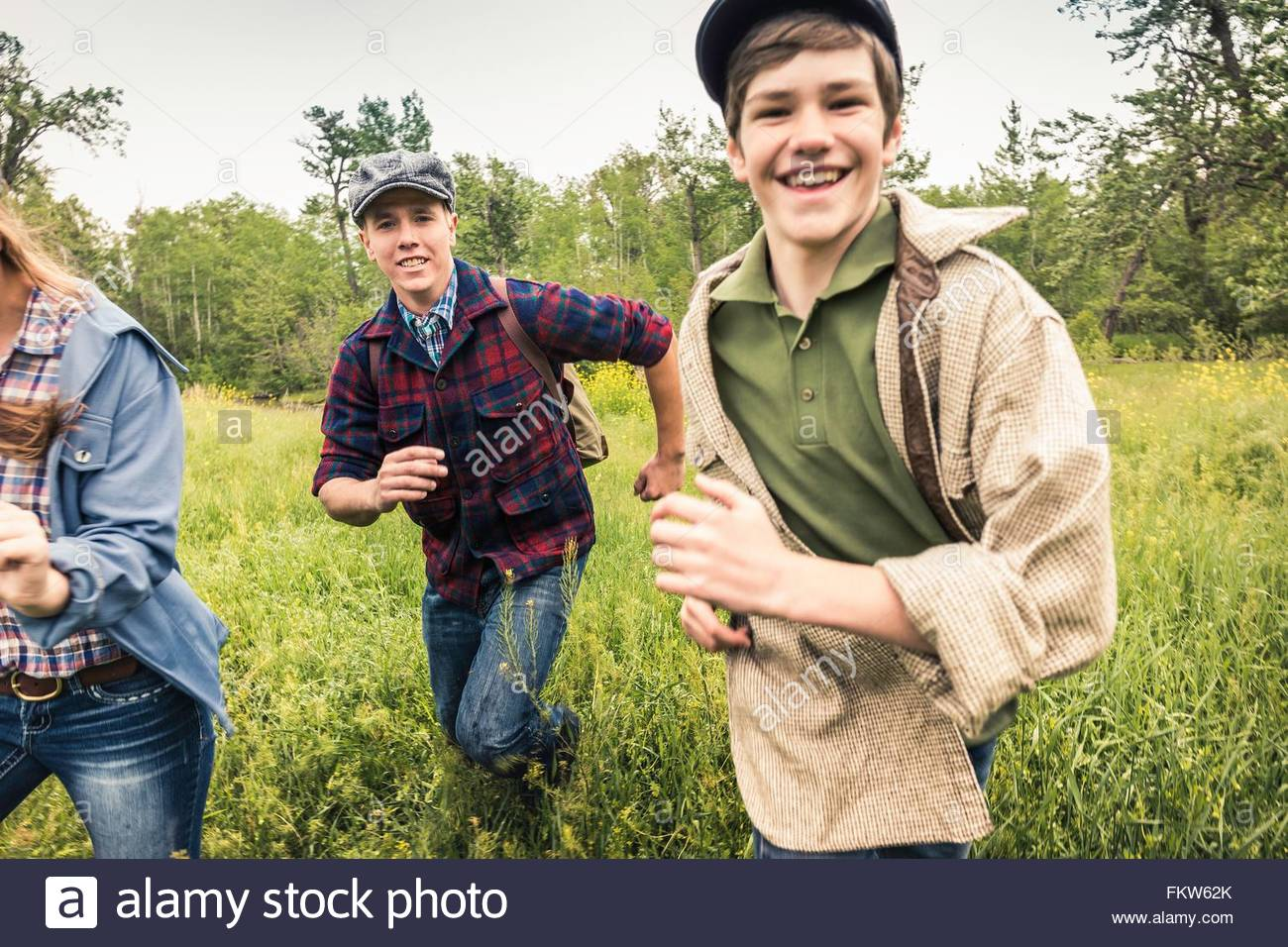 Young adults and teen boy wearing flat caps running in tall grass looking at camera smiling - Stock Image