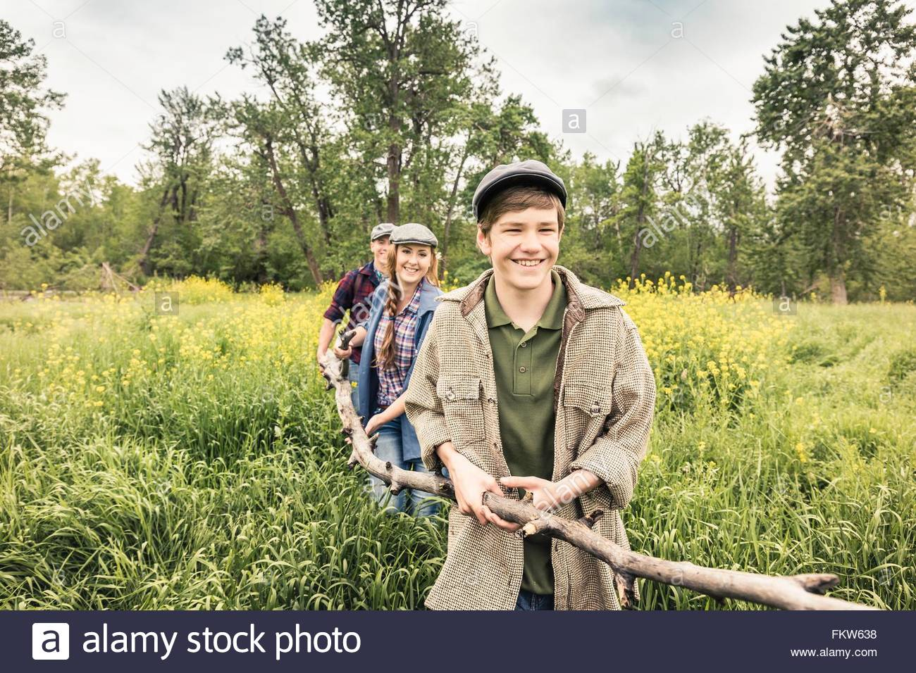 Young adults and teen boy in tall grass carrying branch smiling - Stock Image
