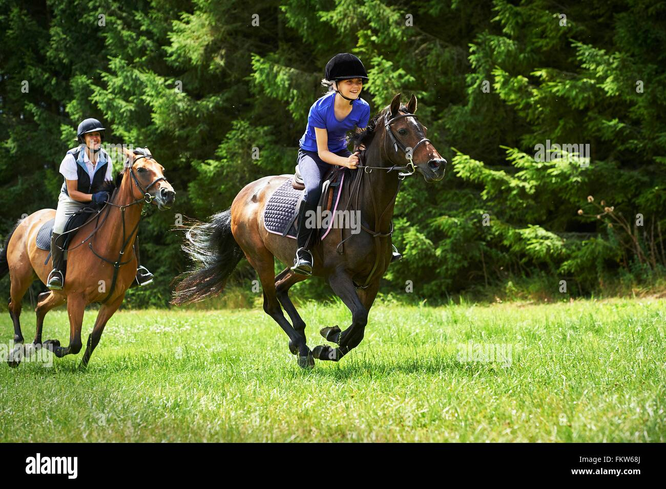 Mature woman and girl galloping on horse Stock Photo