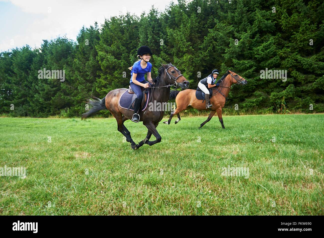 Side view of girl and mature woman wearing riding hats galloping on horseback - Stock Image