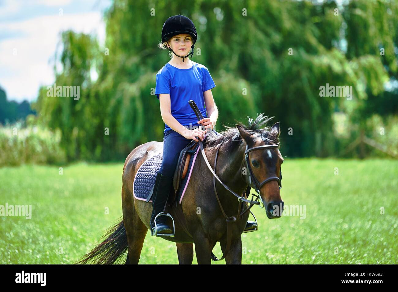 Front view of girl on horseback wearing riding hat looking at camera smiling - Stock Image