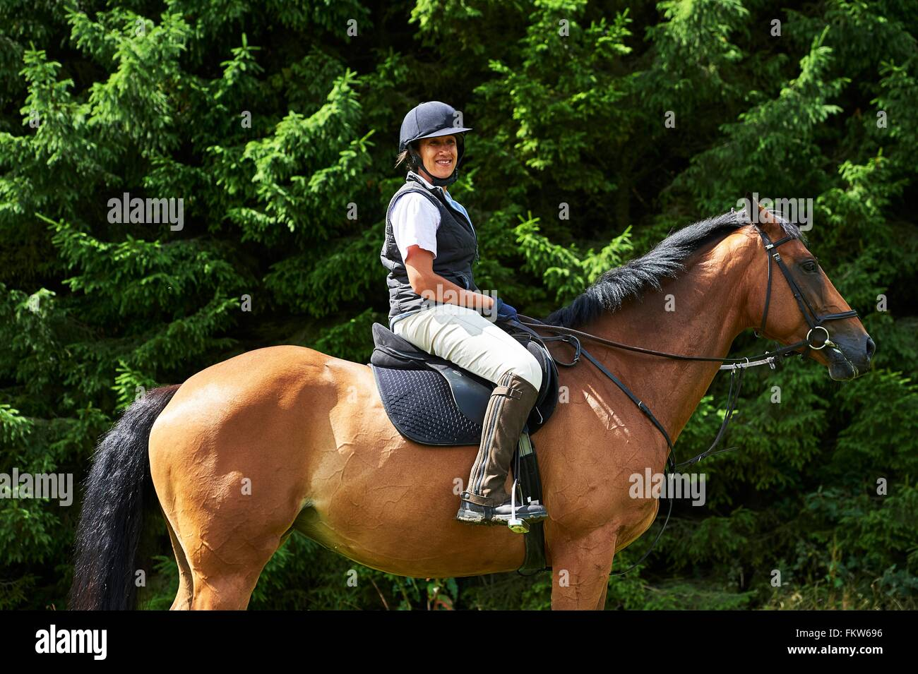 Side view of mature woman on horseback wearing riding hat and boots looking at camera smiling - Stock Image