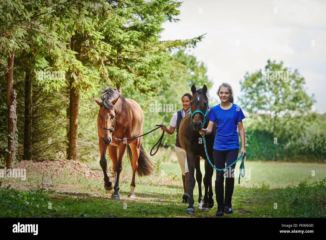 Full length front view of girl and mature woman holding lead rope, walking with horses looking at camera smiling - Stock Image