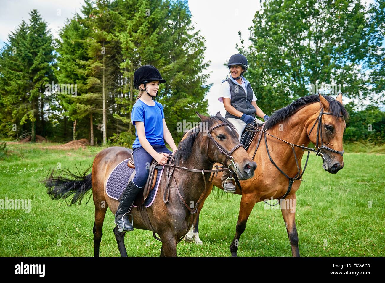 Mature woman and girl on horseback wearing riding hats smiling - Stock Image