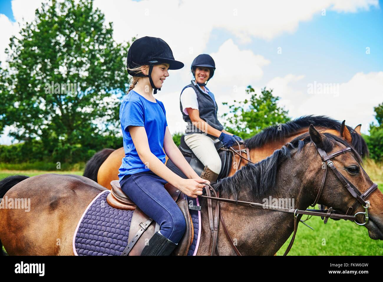 Side view of mature woman and girl on horseback wearing riding hats smiling Stock Photo