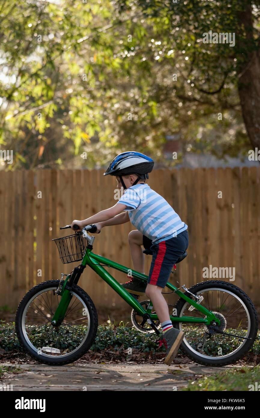 Boy riding bicycle past wooden fence - Stock Image