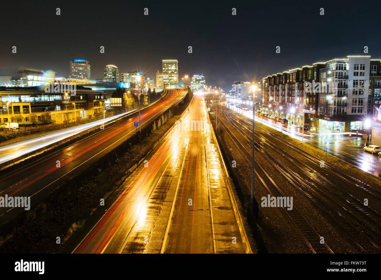 Cityscape with flyover next to rail track at night, Tacoma, Washington, USA - Stock Image