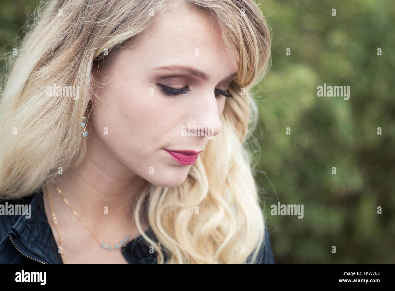 Portrait of young blonde haired woman looking down Stock Photo