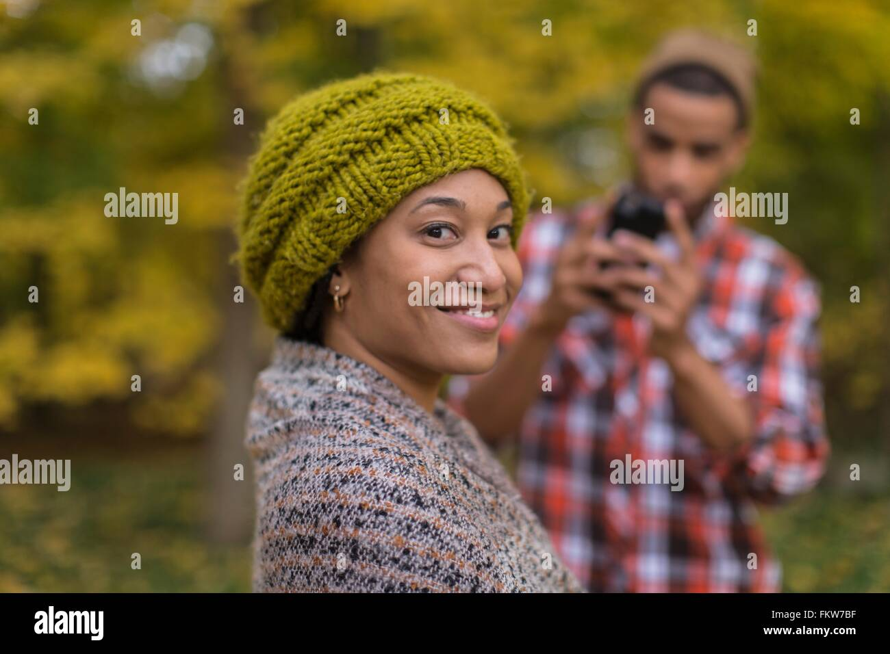 Portrait of mid adult woman being photographed by boyfriend in autumn forest - Stock Image