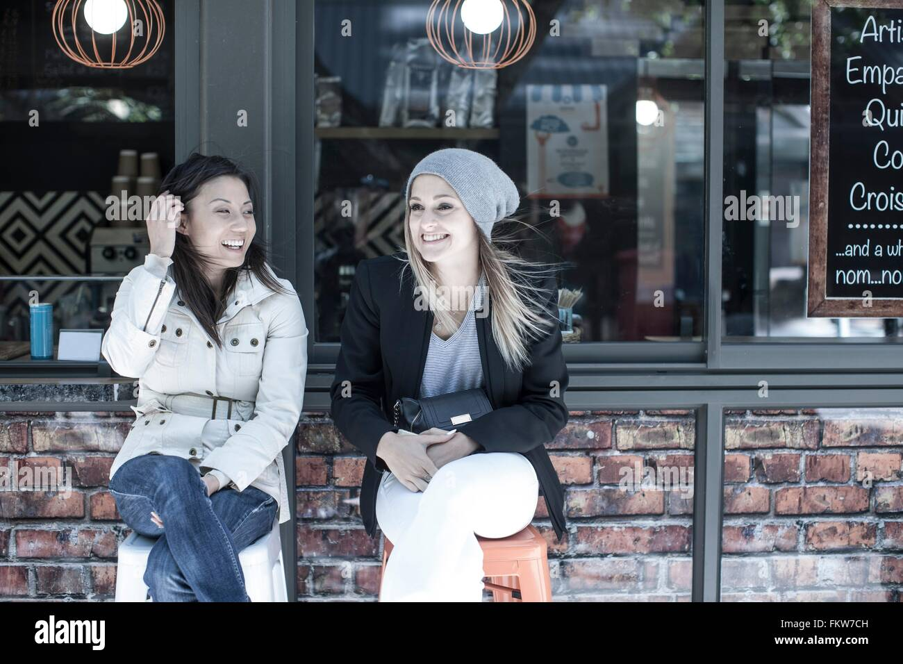 Two women friends sitting outside city cafe - Stock Image