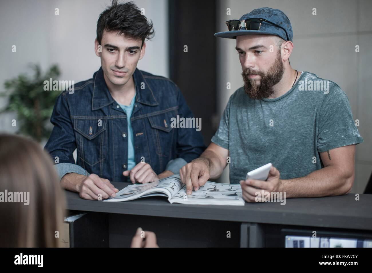 Two young men making query at office reception - Stock Image
