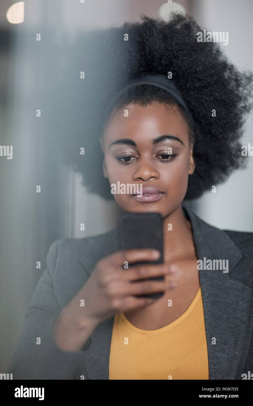 Young businesswomen reading smartphone text at office - Stock Image
