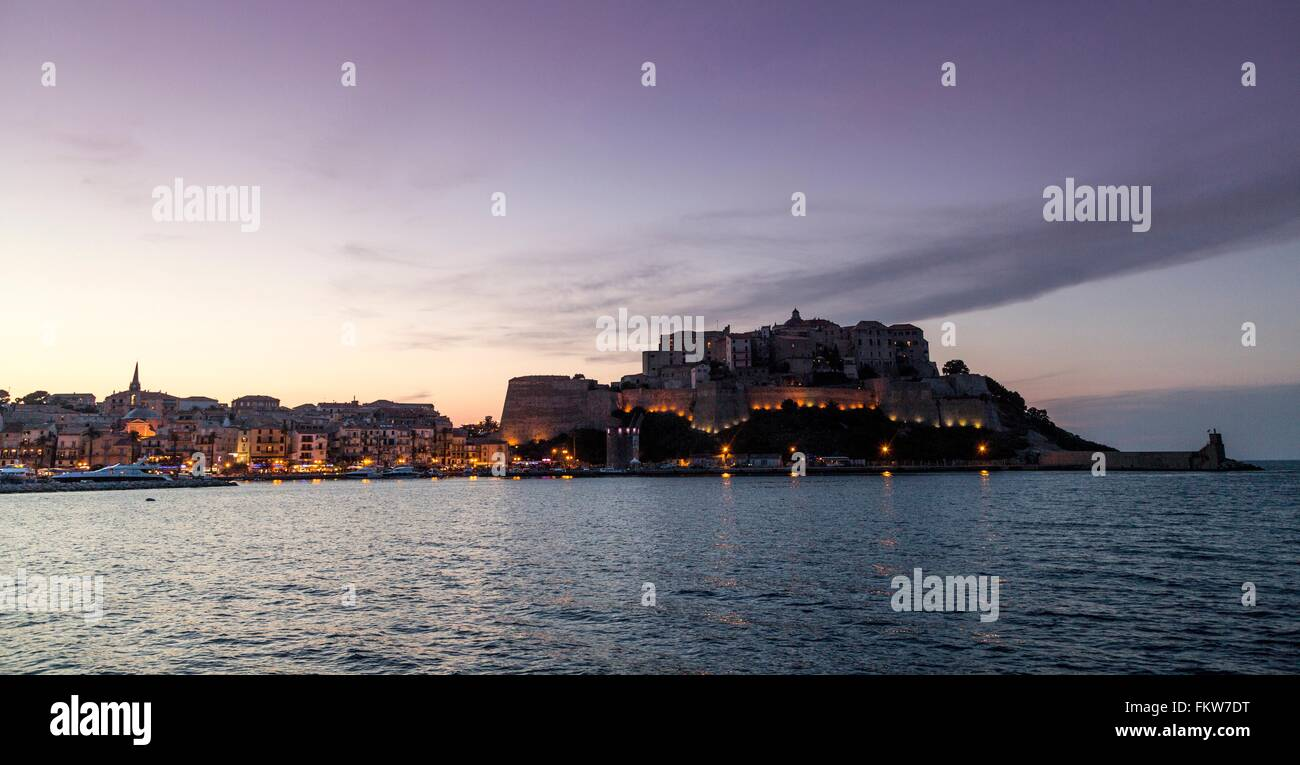 Silhouetted view   sea and Calvi at dusk, Corsica, France - Stock Image