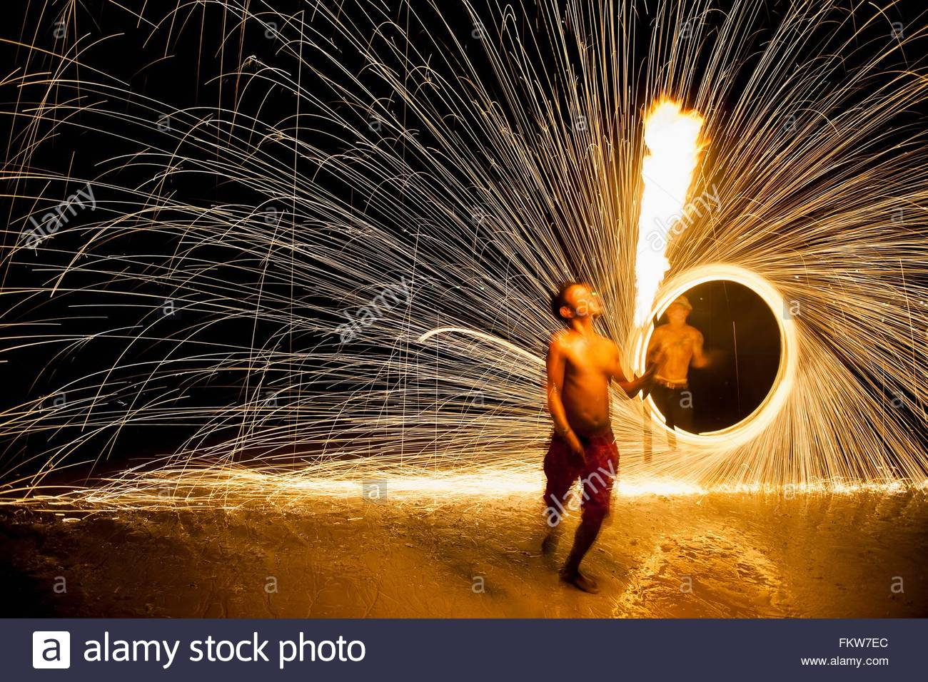 Young man displaying a fire poi show on the beach, Koh Samet, Thailand - Stock Image