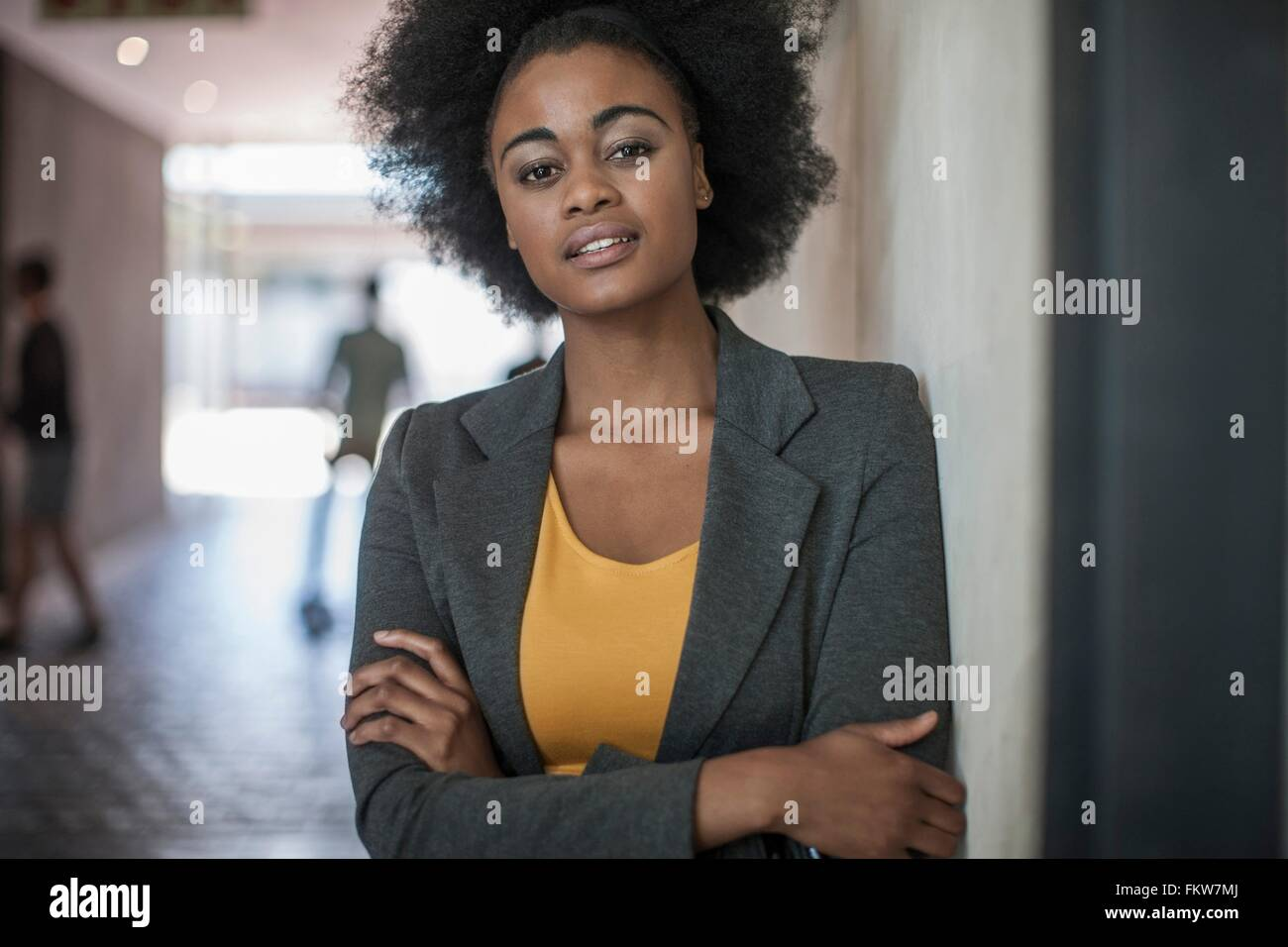 Portrait of confident young businesswomen leaning against office wall - Stock Image