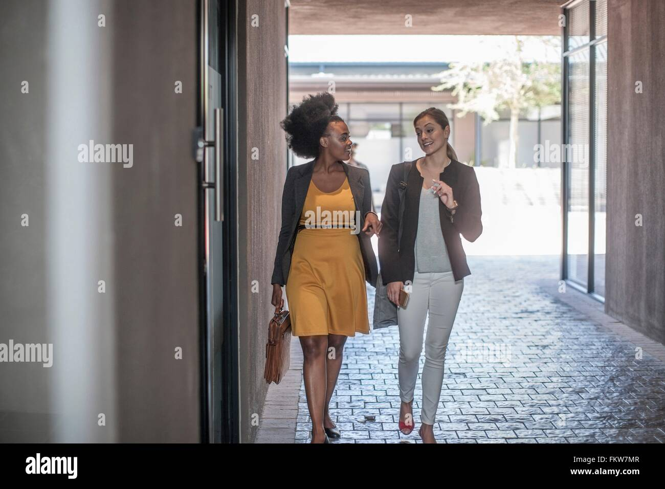 Two young businesswomen walking and talking outside office - Stock Image
