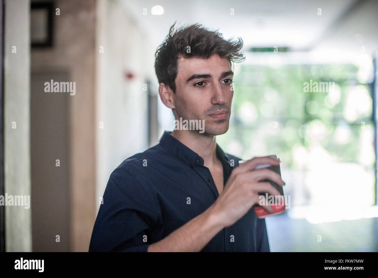 Serious young businessman drinking takeaway coffee in office - Stock Image