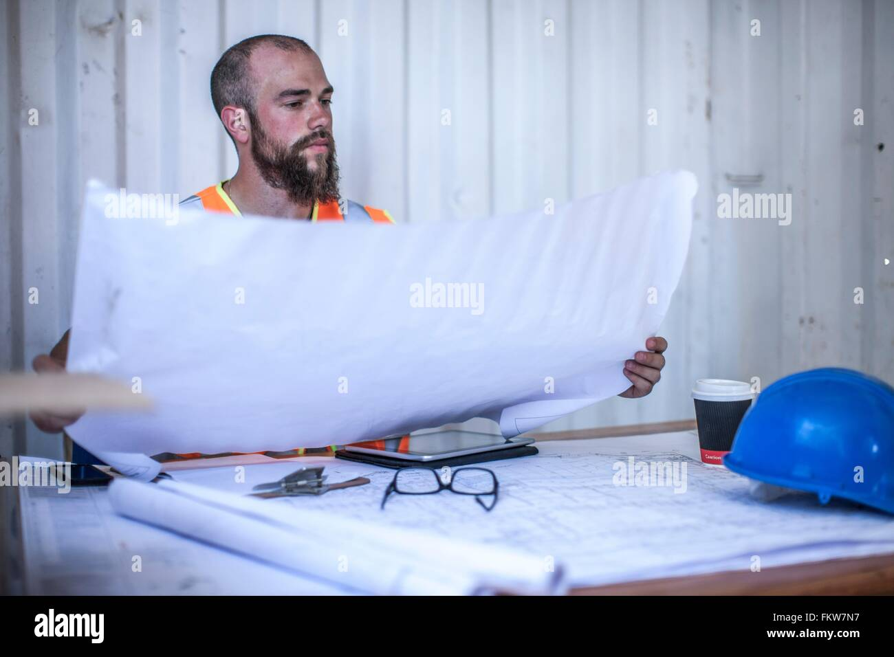 Construction worker sitting at desk looking at blueprint in portable cabin - Stock Image