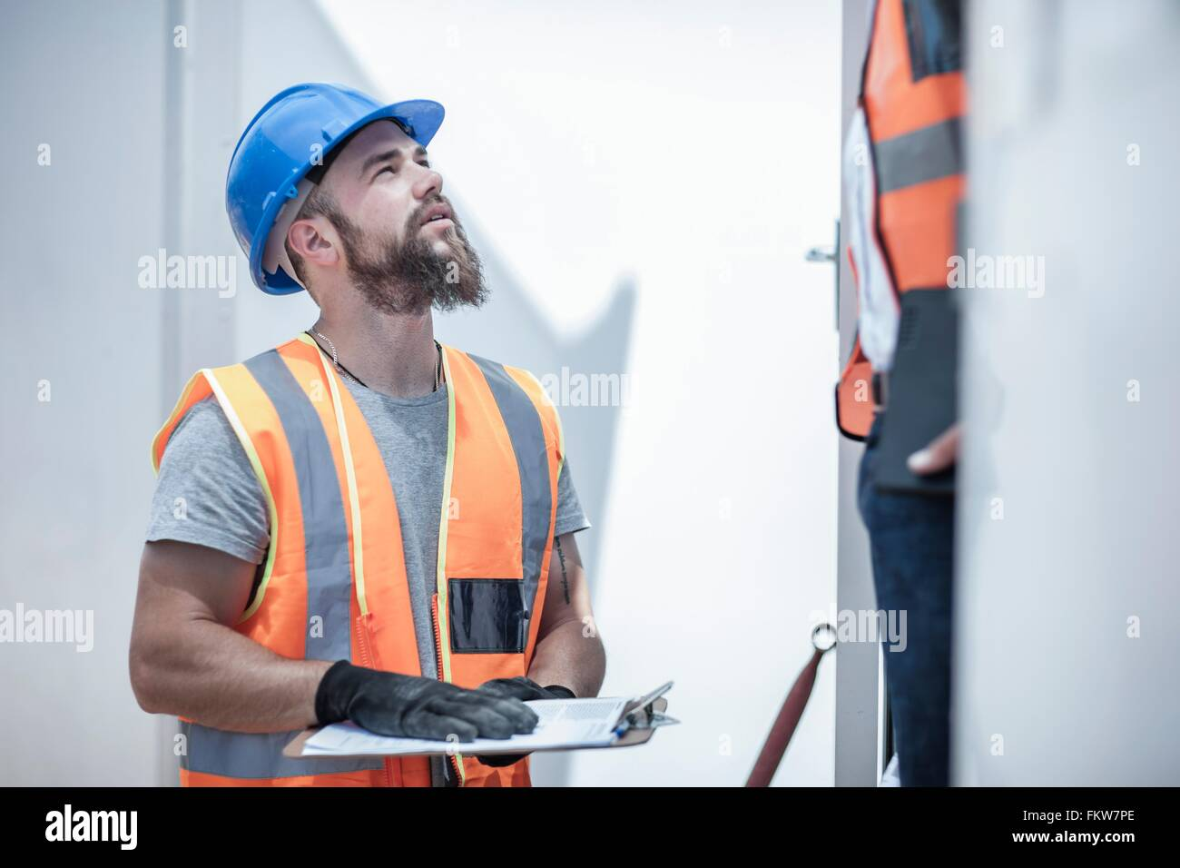 Construction worker talking to foreman from doorway of cabin on construction site - Stock Image